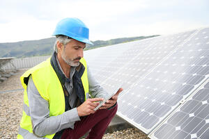 Mature engineer on building roof checking solar panels-1
