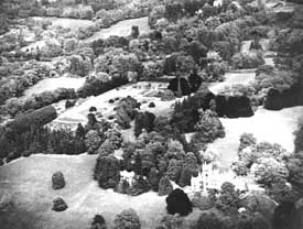 Aerial view of an estate with a house, lawns, gardens, and trees.